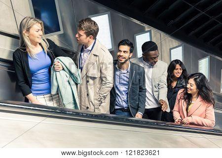 Group of people on the escalator. They are a mixed group of persons they could be friends or just strangers. Urban lifestyle and transportation concepts.