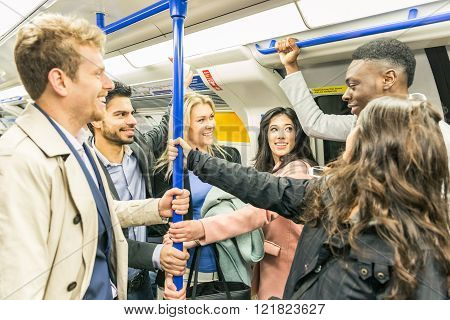 Group of people on tube train in London. They are a mixed group of persons wearing smart casual clothes. They could be friends or just strangers. Urban lifestyle and transportation concepts.