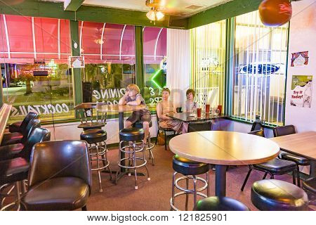 LAKE HAVASU USA - JULY 8 2008: family enjoys the typical pizza restaurant and Bar in Lake Havasu and watches TV while dining. The bar is illuminated with neon lights.