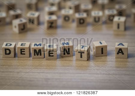 Dementia written in wooden cubes on a table from well ordered to chaotic poster