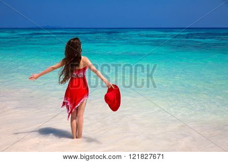 Happy Woman Enjoying On Exotic Beach In Summer By Tropical Blue Water. Attractive Girl In Red Dress