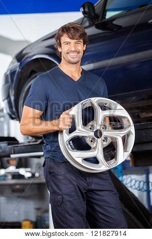 Happy Technician Holding Alloy At Repair Shop