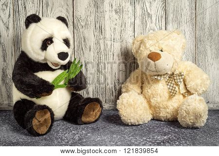 Teddy Bear And Panda Toys Sitting In A Children Room On Wooden Background