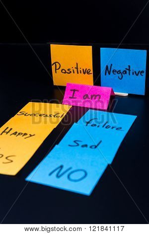 concept of duality using sticky notes with antonyms on a dark background