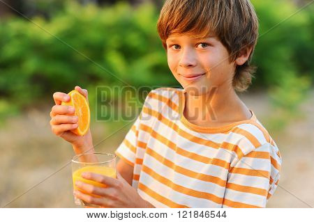 Smiling kid boy 10-12 year old squash orage into glass outdoors. Looking at camera. Healthy lifestyle.