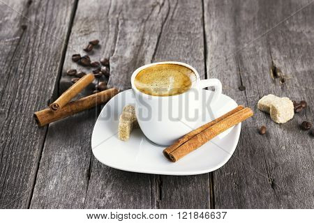 Cup Of Coffee With Cinnamon And Sugar On A Dark Wooden Background