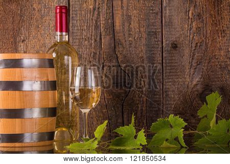 Glass of wine with white bottle barrel grapeleaves and dark wooden background