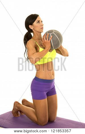 A woman in her fitness clothing on her knee on her fitness mat with her medicine ball working out.
