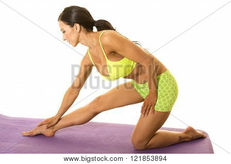 A woman kneeling over stretching out her body.