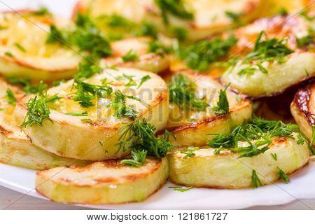 Appetizing vegetable marrows fried in oil and strewed with greengrocery. Close up small depth of sharpness light background