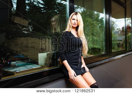 Blonde woman in black short dress sitting on windowsill