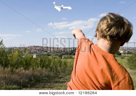 a young boy flying a paper plane