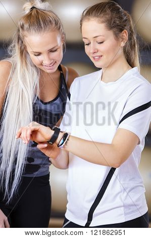 Smiling women looks at training statistics on smart sports clock