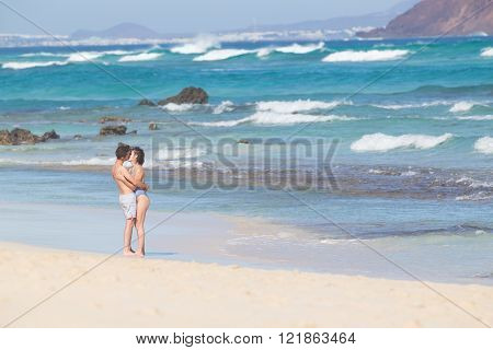 Young couple kissing on sandy beach.
