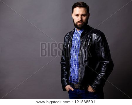 Attractive Young Man Wearing Leather Jacket on gray