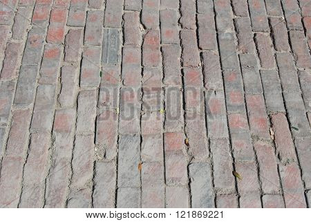 Antique bricks laid out as street cobblestones in a Victorian period setting.