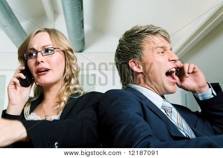 Two business people (male / female) shouting to their mobile phones