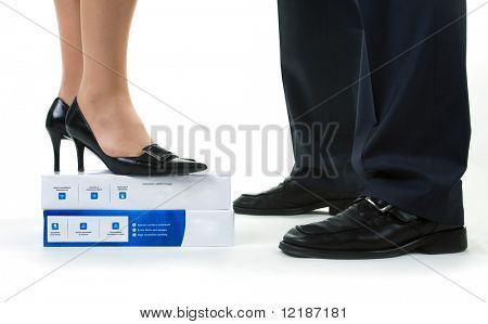 A woman standing on a pack of paper to reach eye level with a man (just feet)