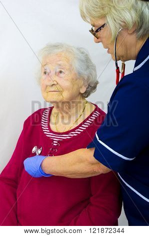 A senior lady having a medical check with a nurse listening with a stethoscope.