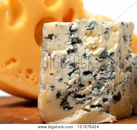 Dorblu and other cheeses on wooden kitchen board