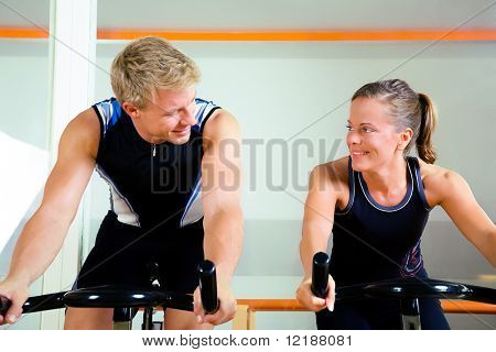 Couple Using Bikes In A Club, Looking At Each Other