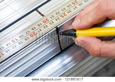 Hand holding marker pen marking measurement on a metal stud