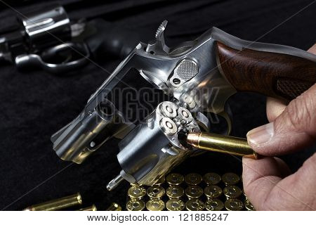 Man loading compact magnum revolver firearm Closeup