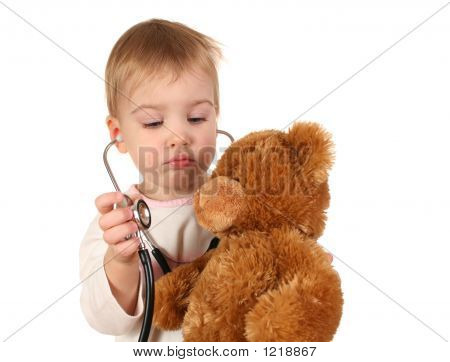 Bebé con un estetoscopio y oso de peluche