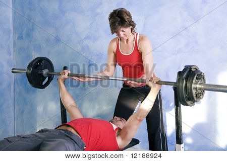 Man lifting a barbell being assisted by a personal trainer