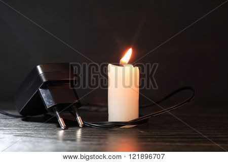 Blackout concept. Electric charger with cable near lighting candle on dark background