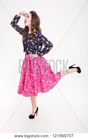 Full length of pretty amusing young woman standing and looking far away over white background