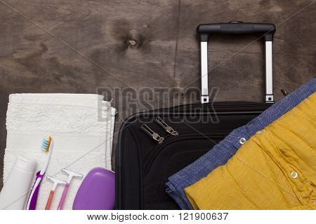 Suitcase traveler toiletries on a wooden background.