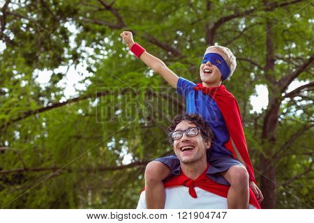 Father and son pretending to be superhero in park