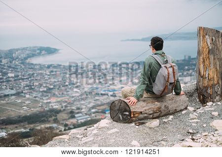Backpacker young man sitting on fallen tree trunk and looking at sea bay