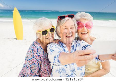 Senior woman taking selfie on the beach