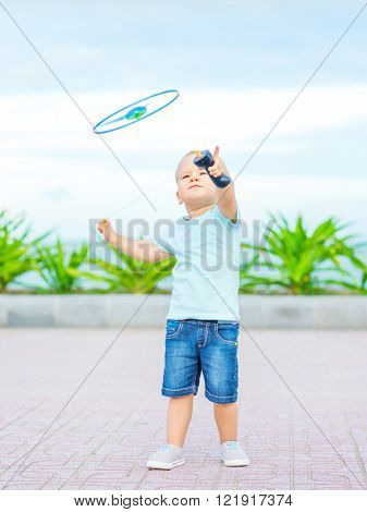 Boy with flying saucer outdoor. Leisure activity poster