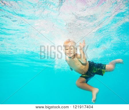 Cute caucasian boy enjoys of swimming underwater