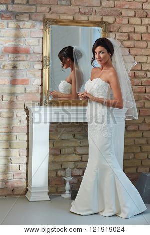 Bride in white wedding dress and veil standing front of mirror. Full size.