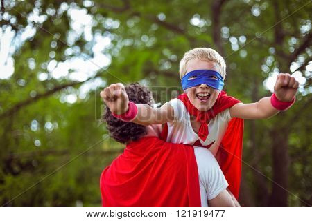 Father and son dressed as superman in the garden