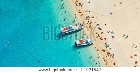 Aerial view of a beach with motorboats and people