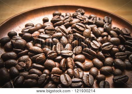 Coffee beans on the wood dish focus at center and blur around