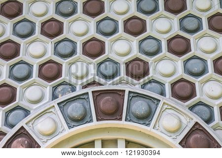 Old and weathered round in the hexagon pattern on the wall
