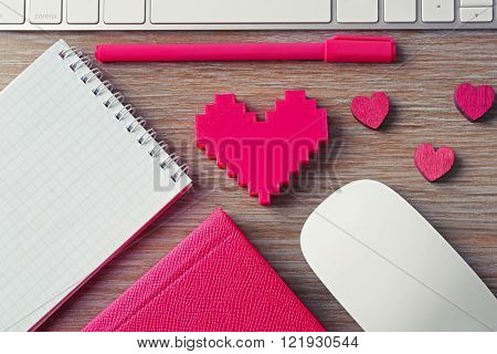 Computer peripherals with pink hearts, pen and notebooks on wooden table