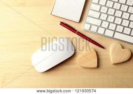 Computer peripherals with wooden hearts, pen and notebook on light wooden table
