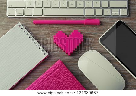 Computer peripherals with pink heart, notebooks and mobile phone on wooden table