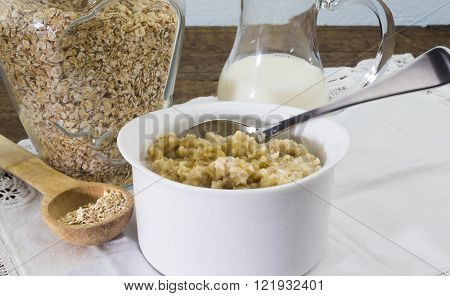 Bowl of cooked rolled oats with milk and honey