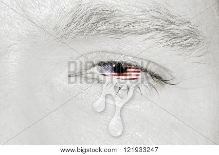 Crying eye with American Flag iris on black and white face. concept of sadness for America pain, war and desease, patriotic metaphor