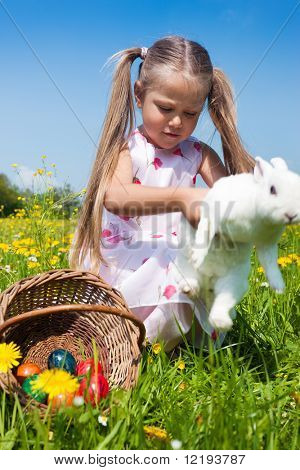 Child hunting the Easter bunny on a spring meadow, eggs in a basket and lots of flowers also to be seen. The animal seems to be escaping