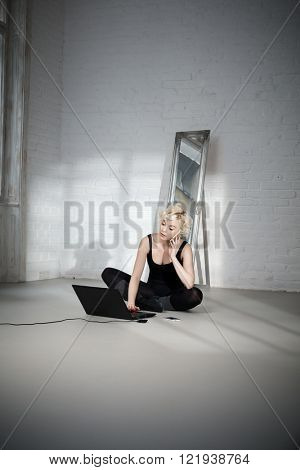 Blond female dancer sitting on floor in ballet studio, using mobilephone and laptop computer.