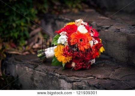 Bright autumn bunch of flowers on the stone stairs. Bouquet for bride comprised by roses sunflower viburnum and gerbera and other autumn flowers.